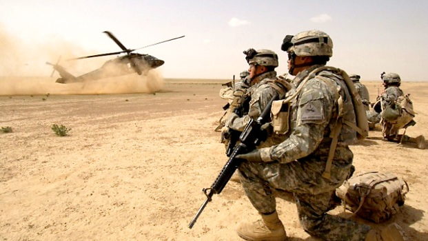 060322-F-7823A-121 U.S. Army soldiers assigned to the 1st Brigade, 1st Armored Division wait to board a UH-60 Black Hawk helicopter during an air assault mission in the Al Jazeera Desert, Iraq, on March 22, 2006. DoD photo by Staff Sgt. Aaron Allmon, U.S. Air Force. (Released)