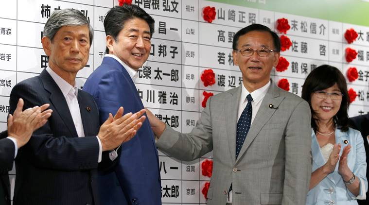 Japan's Prime Minister Shinzo Abe, who is also leader of the ruling Liberal Democratic Party, smiles with party senior members as they put a rosette on the name of a candidate who is expected to win the upper house election in Tokyo, Japan